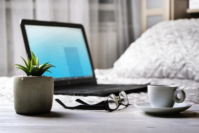 Laptop with blank screen on bed. Comfotable working at home. Glasses, cup of coffee and flower on bedside table. Modern. Bedroom interior. Selective focus royalty free stock image