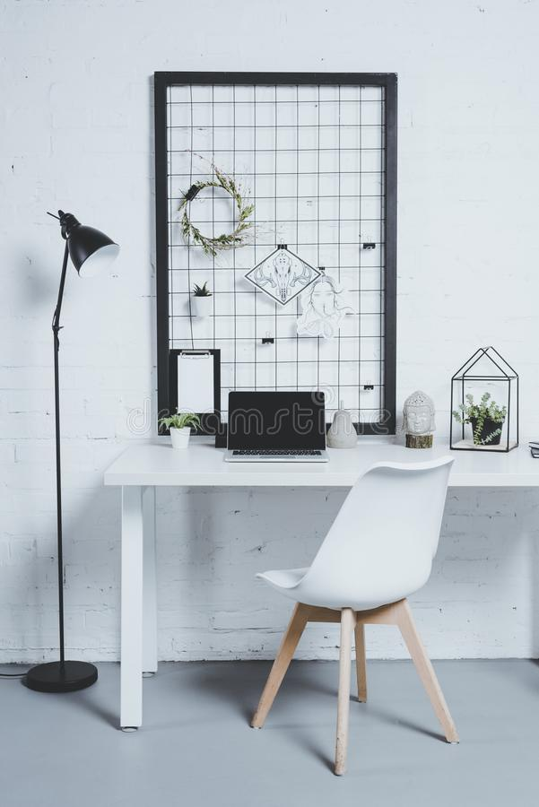 laptop with blank screen and plants on table in modern office stock image