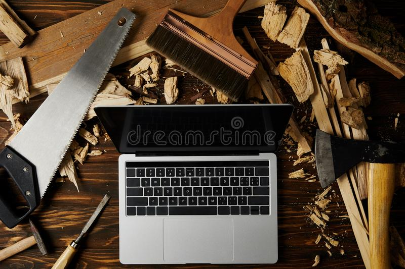 laptop with blank screen surrounded by axe, handsaw, chisel, paintbrush and hammer on wooden table stock photography