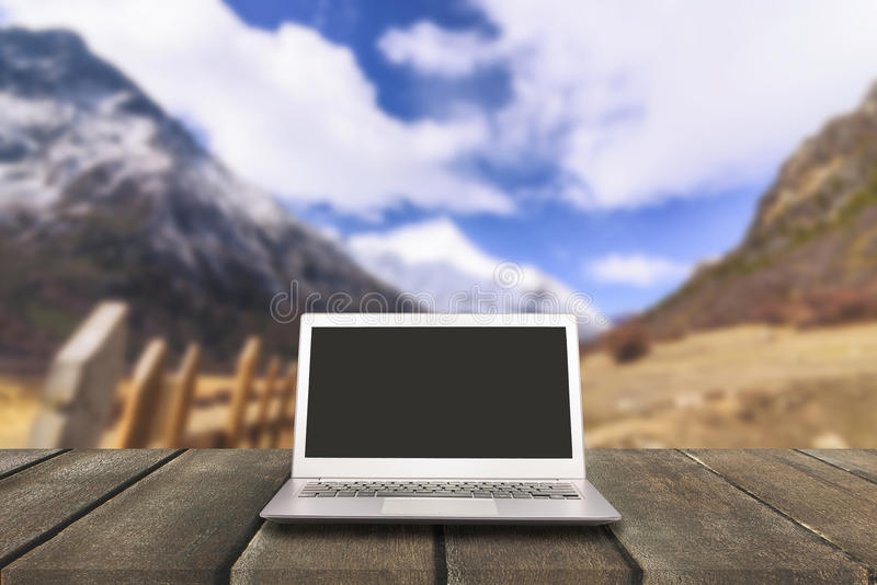 Laptop with blank screen on wooden table with forest in mountain royalty free stock image
