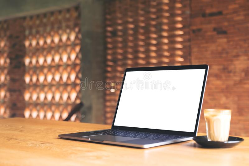 Laptop with blank white desktop screen and coffee cup on wooden table with brick wall background. Mockup image of laptop with blank white desktop screen and stock photography