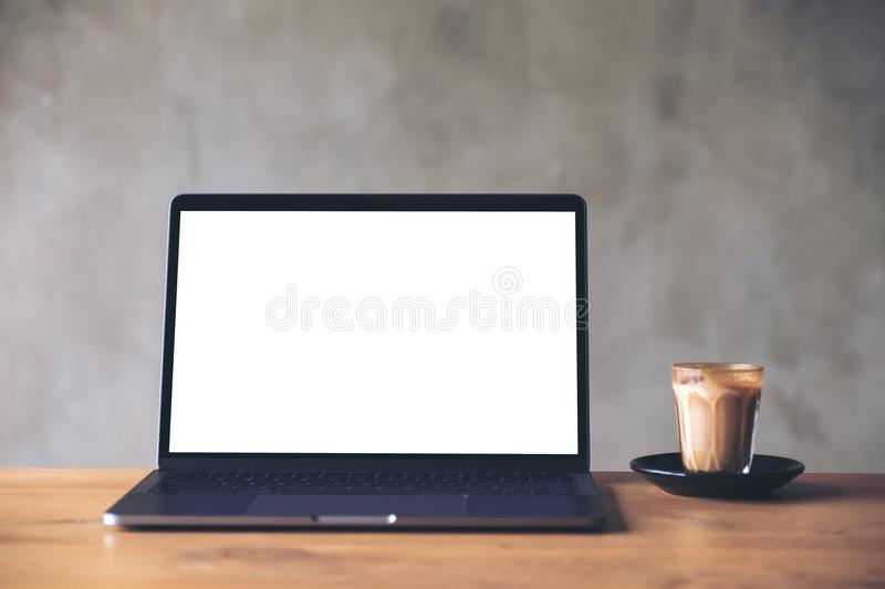 Laptop with blank white desktop screen and coffee cup on wooden table with concrete wall background. Mockup image of laptop with blank white desktop screen and royalty free stock photography