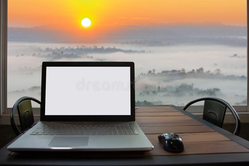 Laptop with blank white screen for mock up template background on table with view of sunrise over mountain stock photos
