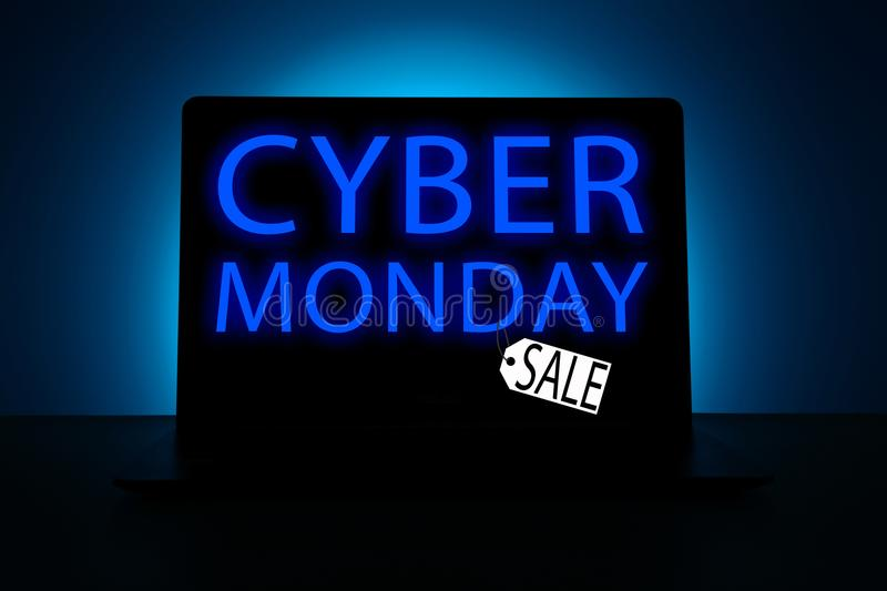 Laptop glowing with inscription Cyber Monday. Laptop on blue background glowing in dark showing words Cyber Monday Sale royalty free stock image