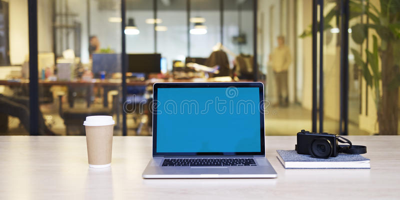 Laptop with blue screen in office. A laptop computer with blue screen, together with a camera and a cup of coffee on desk in a small stylish office stock image