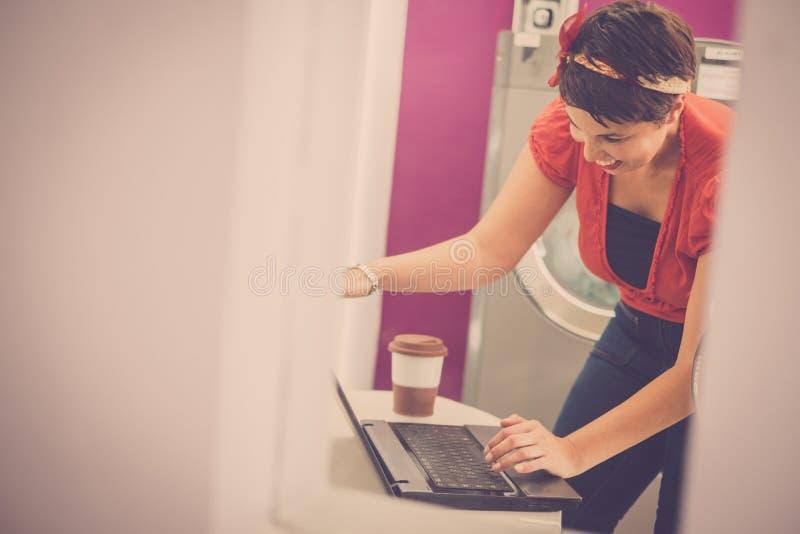 Laptop bonito novo caucasiano alegre do uso da mulher que espera na lavagem automática pela roupa limpa - cidade urbana do tof do imagem de stock royalty free