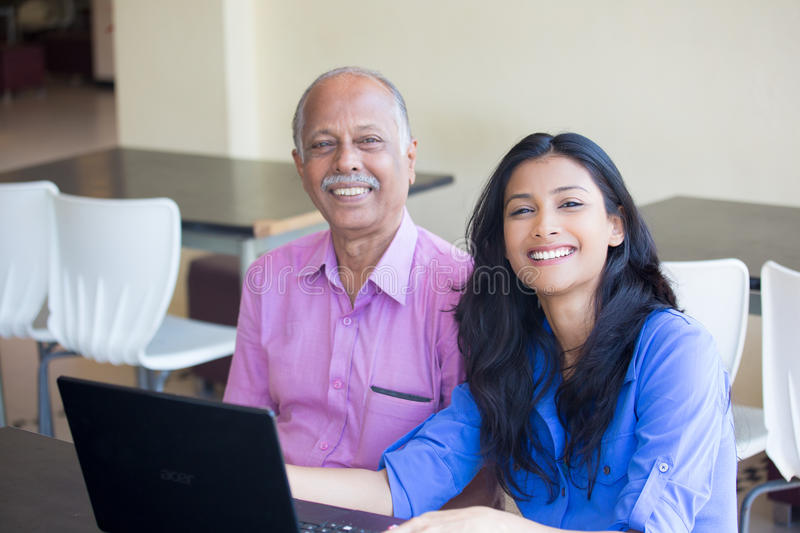 Laptop browsing. Closeup portrait, sitting young women showing elderly men to use black laptop, smiling pose , indoors background royalty free stock images