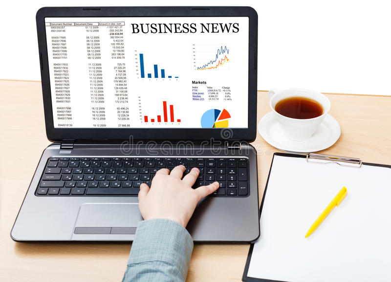 Laptop with business news on screen on office desk. Business still life - laptop with business news on screen on office desk isolated on white background stock photos