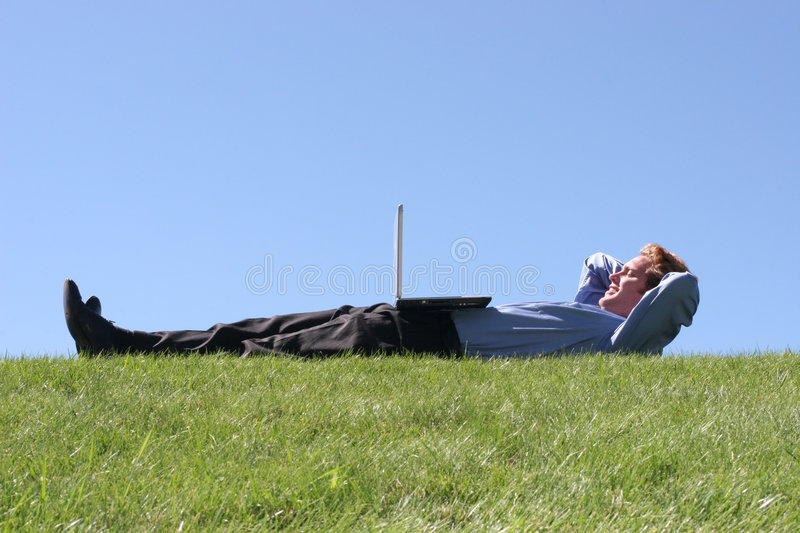 Laptop on businessman on grass stock photos