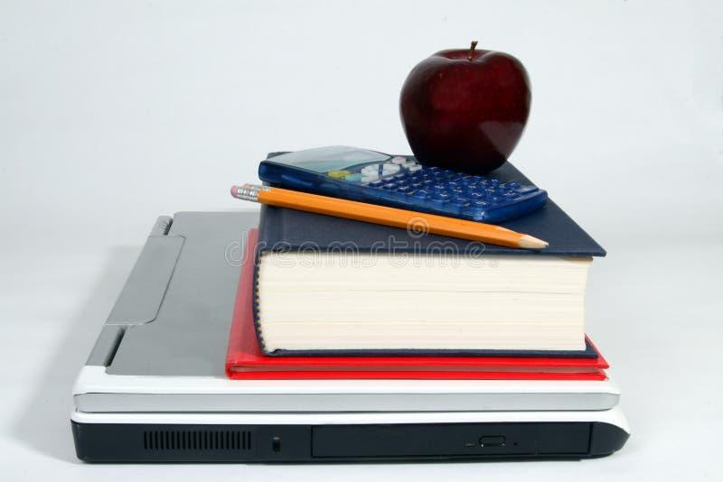 Laptop, calculator, boeken, appel en potlood stock foto's