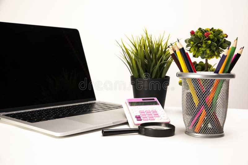 Laptop, calculator, magnifier, organizer, crayons and two green plants neatly placed on a clean white desk royalty free stock images