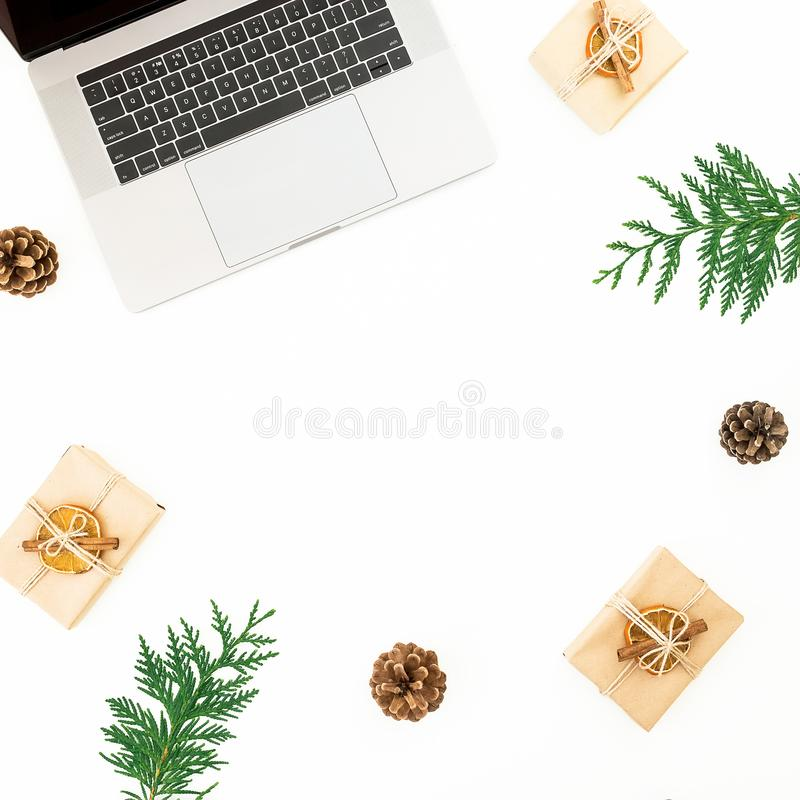 Laptop with Christmas gifts, evergreen branches and pine cones on white background. Holiday office composition. Top view. Flat lay. Laptop with Christmas gifts stock image