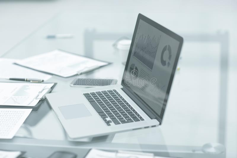Laptop, clipboard and financial data on the businessman`s Desk stock photos