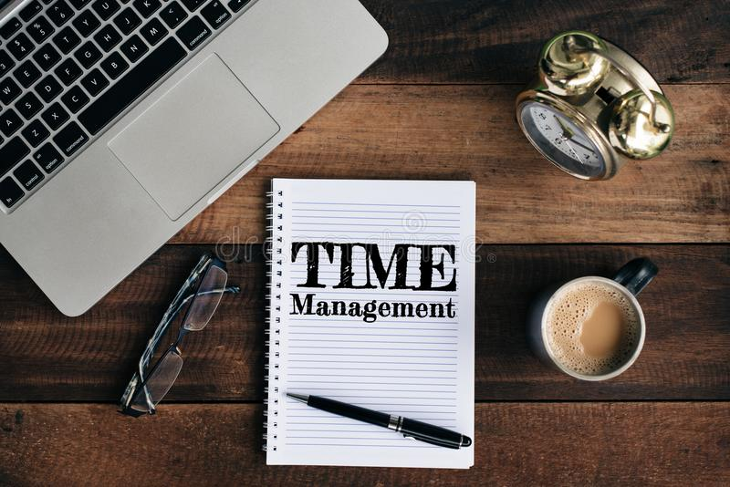 Laptop, clock, glasses, coffee and notebook with TIME MANAGEMENT word on a wooden table. Time management concept stock image