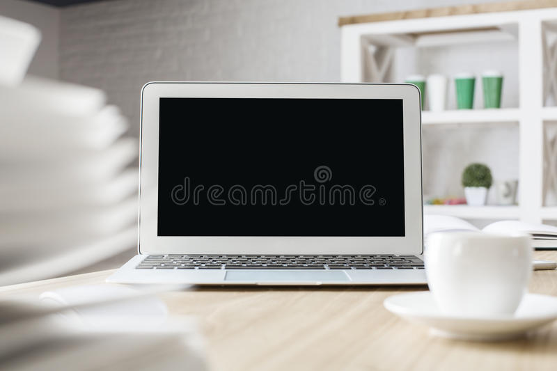 Laptop and coffee cup. Front view of creative workplace with blank laptop, coffee cup and blurry book. Mock up royalty free stock images