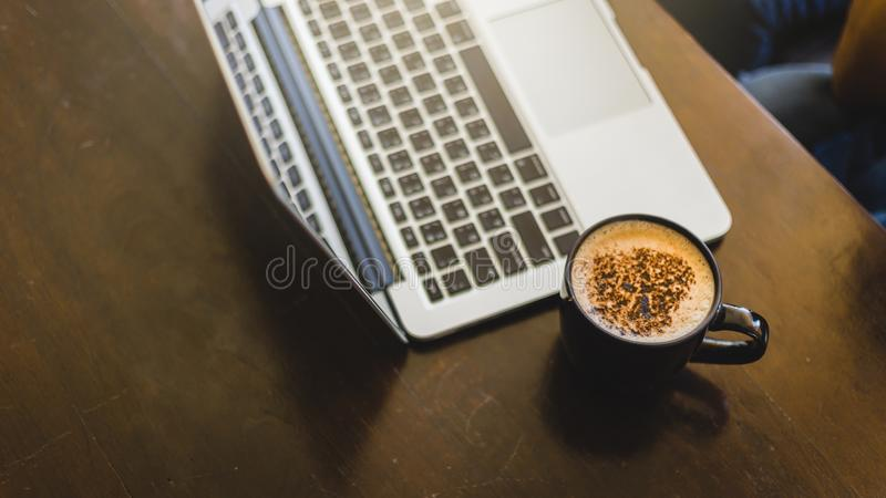 Laptop and coffee cup at his working place in Cafe stock images