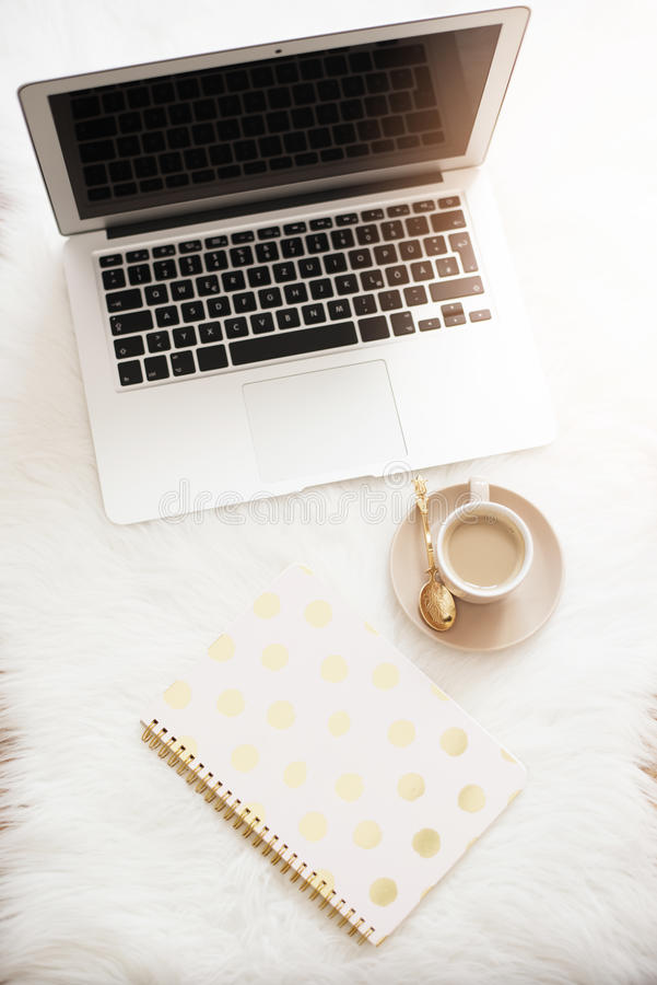 Laptop, coffee and notebook on the floor on a white fur carpet. Freelance fashion comfortable femininity home workspace in flat la stock photo