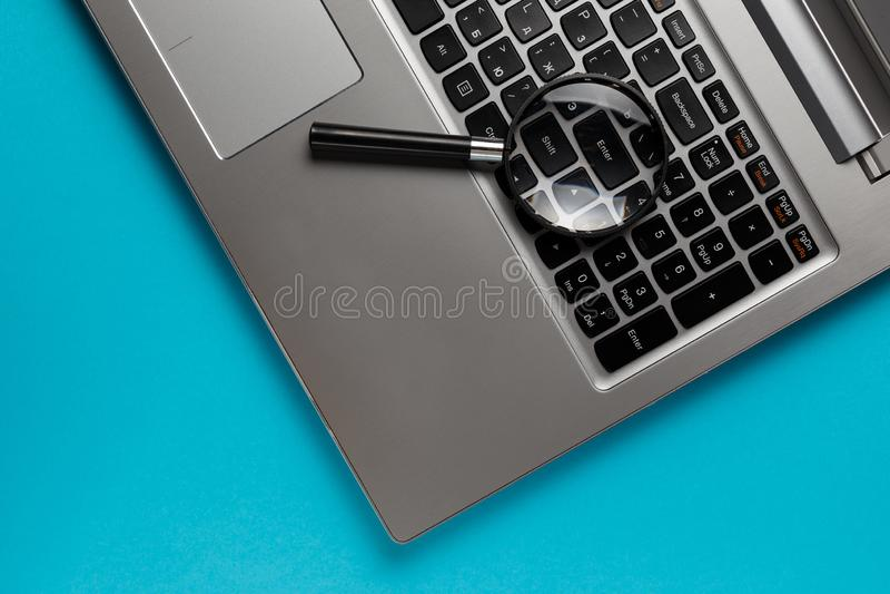 Laptop com a lupa no fundo azul, conceito da busca Imagem conceptual da seguran?a do Internet fotos de stock