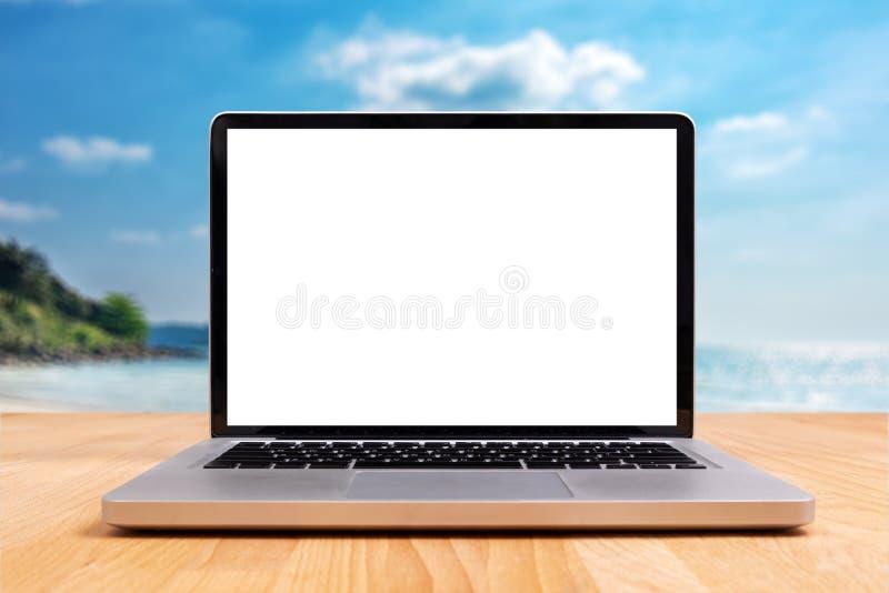 Laptop com a tela branca vazia vazia para o espaço da cópia na mesa de madeira com a praia obscura do oceano do mar do verão no f fotos de stock