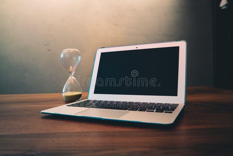Laptop computer accanto all'ora di vetro sulla superficie di legno marrone immagini stock