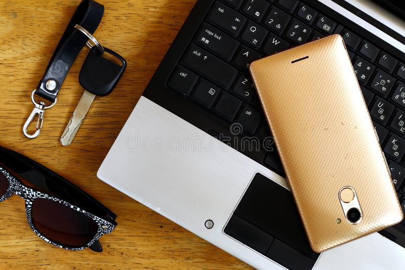 Laptop computer, autosleutel, smartphone en zonnebril stock afbeelding