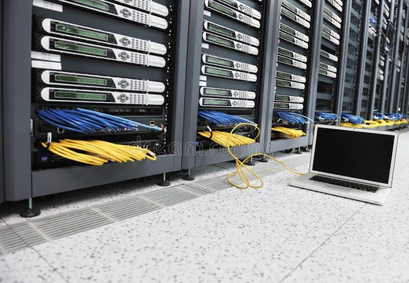 Laptop computer bij de ruimte van het servernetwerk stock foto