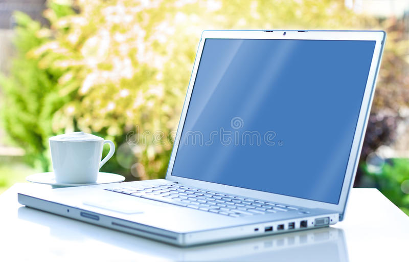 Laptop computer and coffee in the garden. Freelance or remote work concept