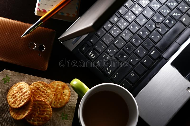 Laptop computer, cup of coffee, ballpen, notebook, crackers, and a smartphone. Overhead photo of laptop computer, cup of coffee, ballpen, notebook, crackers, and royalty free stock image