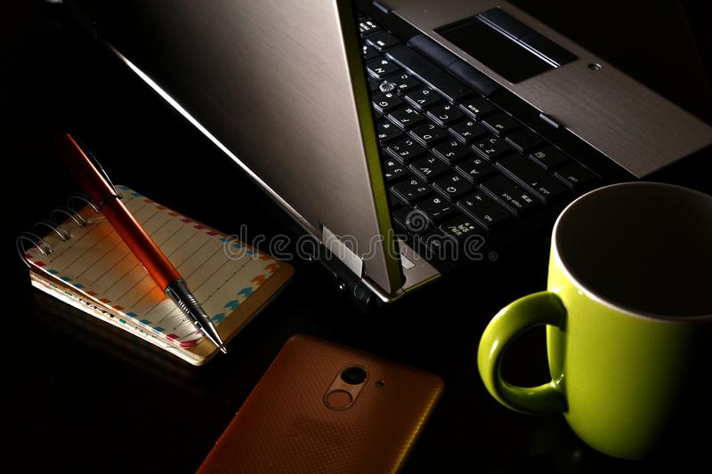 Laptop computer, cup of coffee, ballpen, notebook and a smartphone. Overhead photo of laptop computer, cup of coffee, ballpen, notebook and a smartphone stock photography