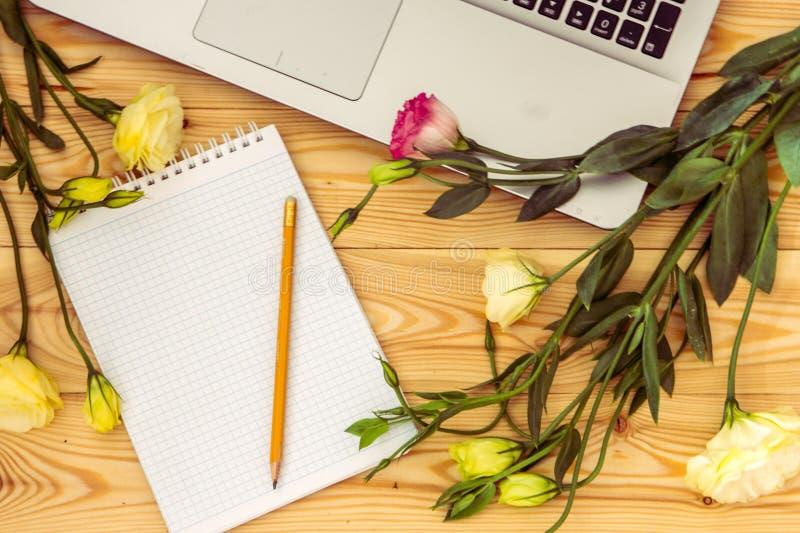 Laptop-Computer, des leeren Papiers, des Bleistifts und des Eustoma Blumen auf Holz stockbilder