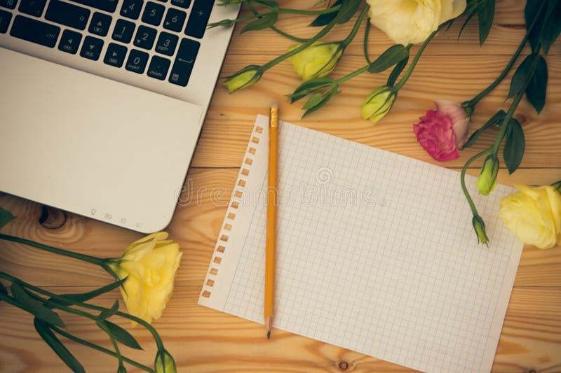 Laptop-Computer, des leeren Papiers, des Bleistifts und des Eustoma Blumen auf Holz lizenzfreie stockfotos