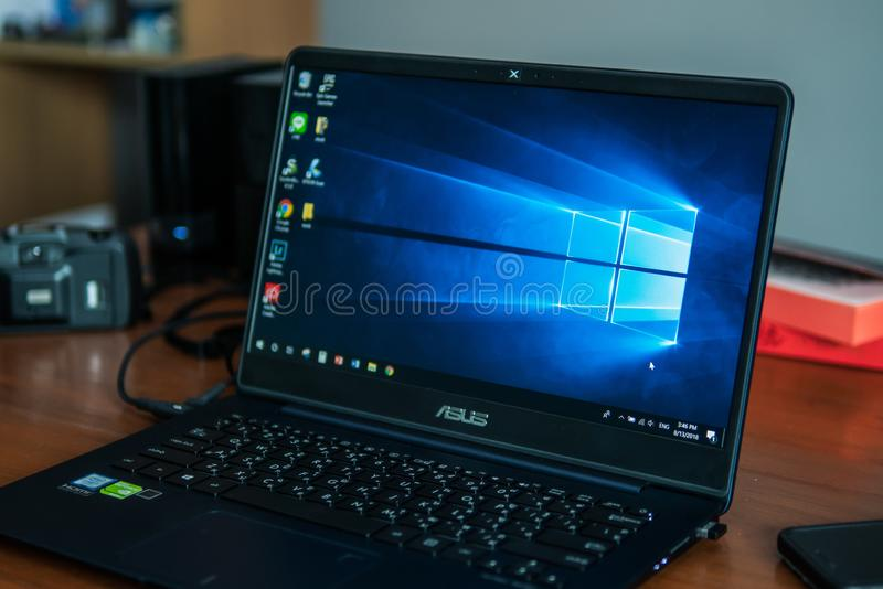 Laptop-Computer, die seinen Schirm mit Microsoft Windows-Logo auf dem Desktop zeigt stockbild