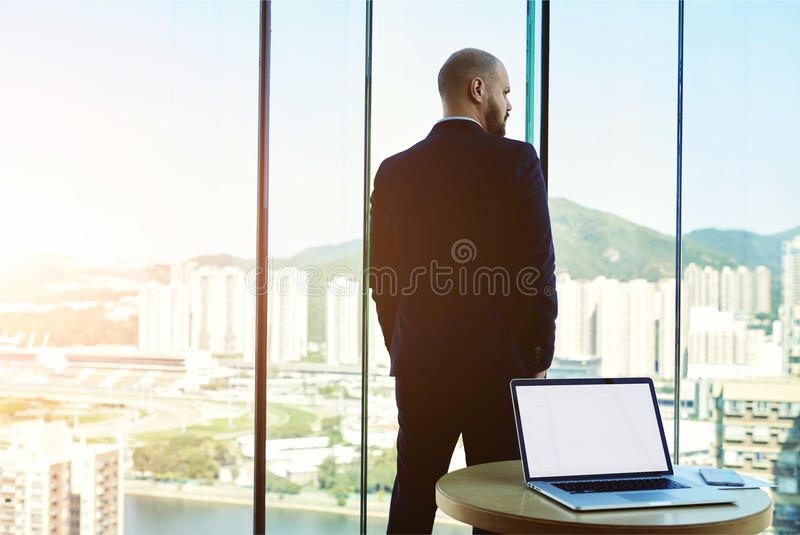 Laptop computer with empty copy space screen. Back view of a confident man CEO is resting after meeting with staff company, while is standing near office window stock images