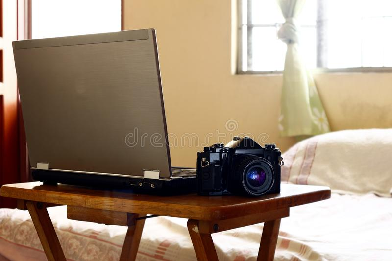 Laptop computer en hand 35mm filmcamera stock afbeeldingen