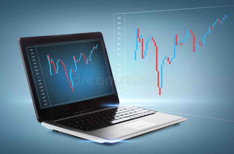 Laptop computer with forex chart on desktop. Technology, money and investment concept - laptop computer with forex chart on desktop stock photography