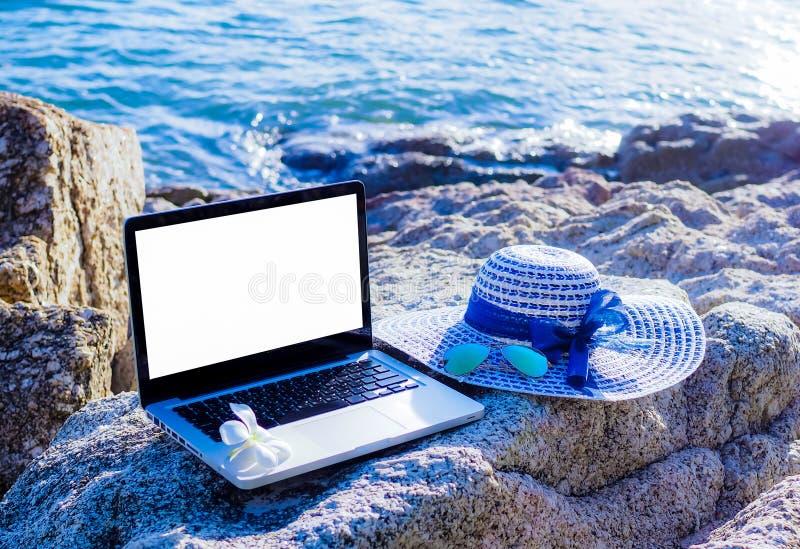 Laptop-Computer funktionieren im Urlaub, Sommer am Strand stockfotos