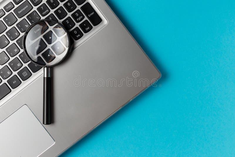 Laptop computer met vergrootglas stock afbeeldingen