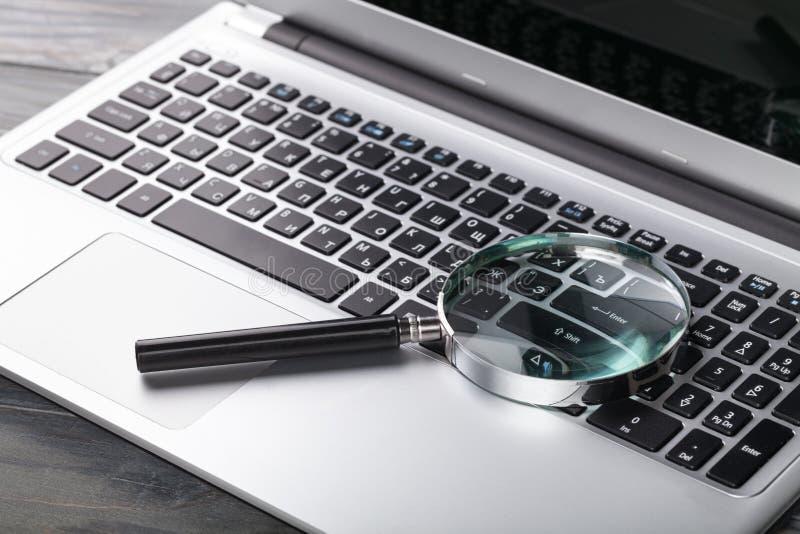 Laptop-Computer mit Vergrößerungsglas lizenzfreies stockfoto