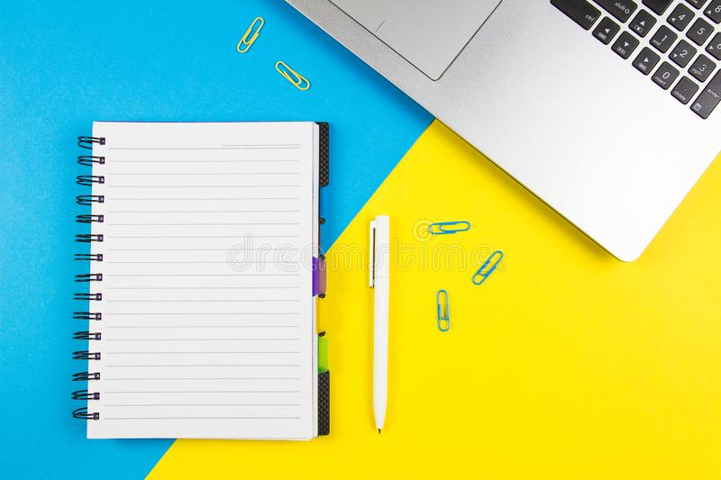 Laptop computer, open paper notebook and white pen on blue and yellow color background. Top view, copy space for text stock photos