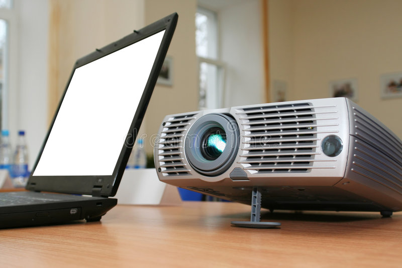 Laptop with computer projector on table stock photography
