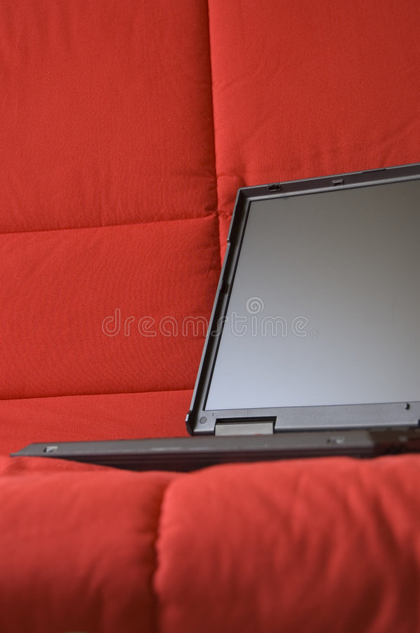 Laptop computer on red couch royalty free stock images