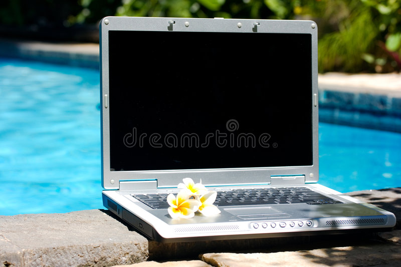 Laptop computer and resort pool royalty free stock photography