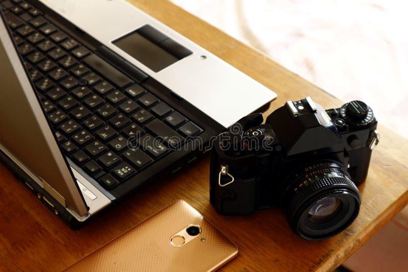 Laptop computer, smartphone en hand 35mm filmcamera royalty-vrije stock foto's