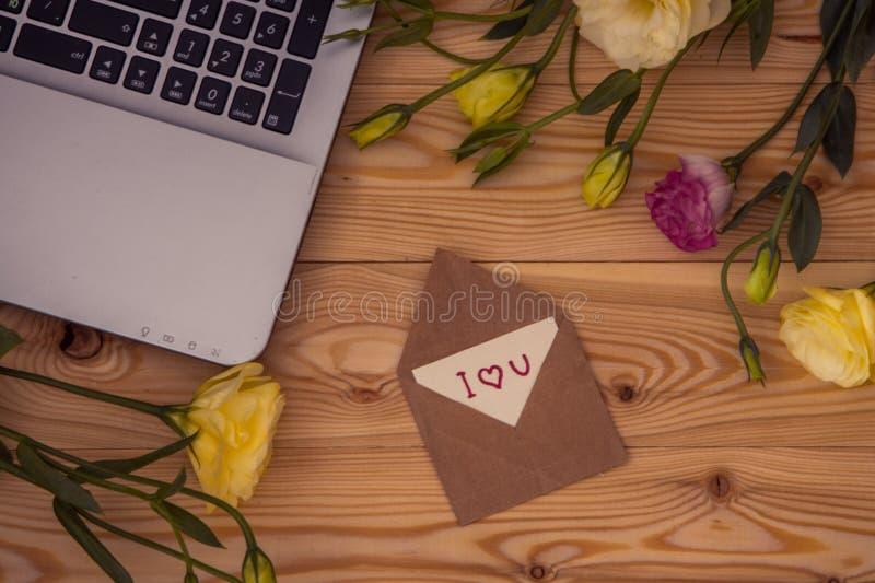 Laptop-Computer, Text ich liebe dich und Eustomablumen auf hölzernem b stockfoto