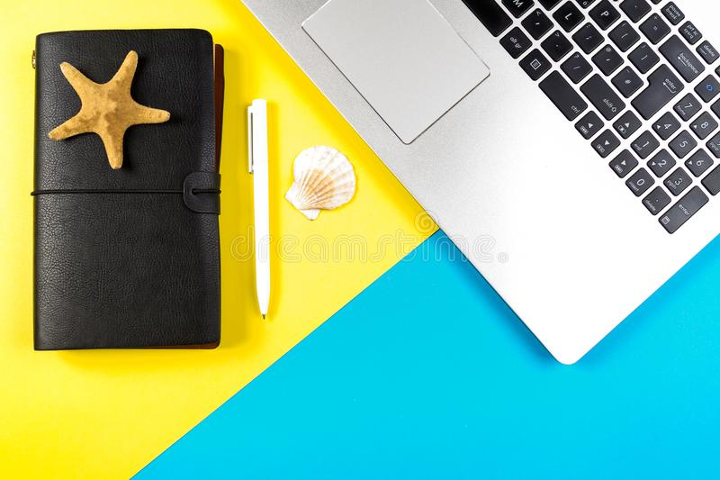 Laptop computer, travel notebook and seashells and starfish over blue and yellow background. stock images