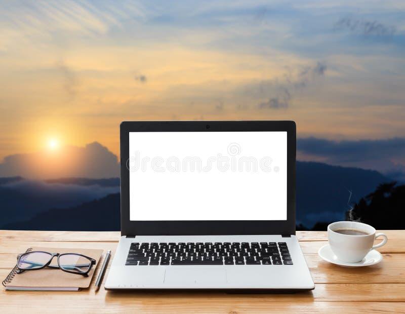 Laptop-Computer und Kaffee auf hölzernem Arbeitsplatz und Berg stockfotos