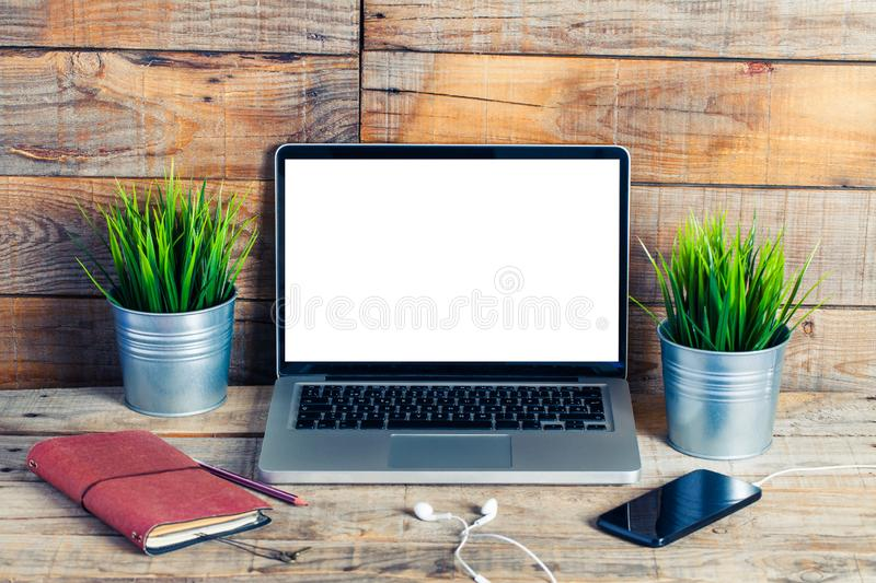 Laptop computer with white blank screen. Placed on a rustic wooden desk stock images
