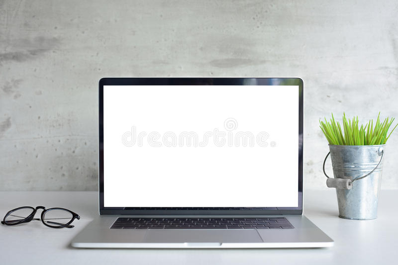 Laptop computer white screen on desk table front view stock photography