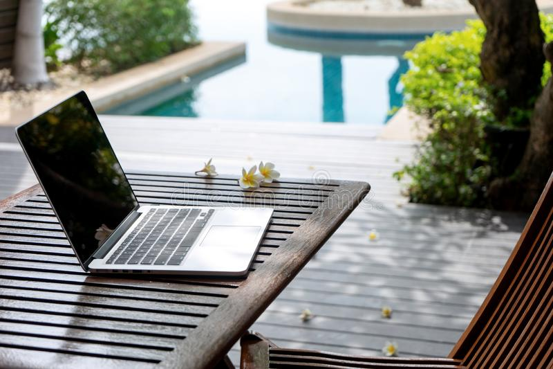 Laptop computer on the wood table. Near the swimming pool, attractive, background, blank, blue, business, businessman, cheerful, communication, concept, desk stock image
