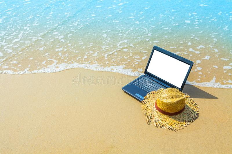 Laptop of computernotitieboekje op overzeese strand en golf - bedrijfstra stock foto's